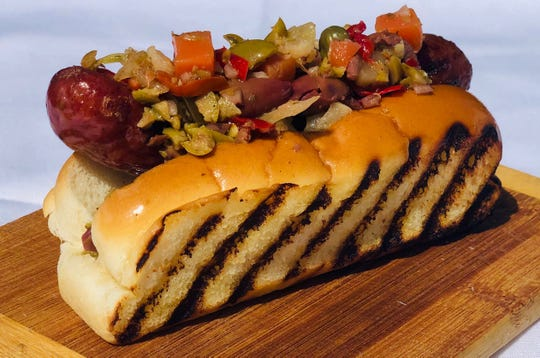"A ""No Bologna Coney"" dog, a mortadella sausage served on a grilled split-top bun and topped with muffaletta olive and pepper salad, from Mancini's al Fresco."