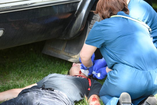 The Scrubs Camp at St. Cloud State stages a bus crash outside North Benton Resident Hall, Tuesday, June 18. Camp members were able to take turns as a responder and a victim in their disaster preparedness simulation.