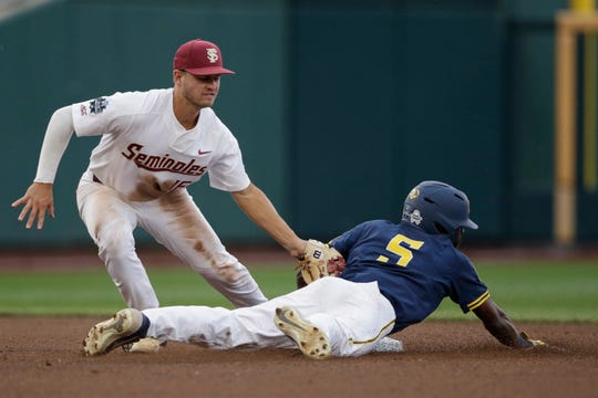 Michigan's Christan Bullock (5) is caught stealing second base by Florida State shortstop Mike Salvatore, left, in the fourth inning of an NCAA College World Series baseball game in Omaha, Neb., Monday, June 17, 2019. (AP Photo/Nati Harnik)