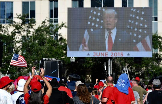 Outside the Amway Center June 18, 2019, crowds react to a video of Donald Trump during his first campaign for president.