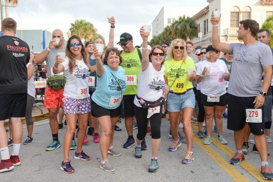 Team Treasure Coast Crusaders, from left, Monique Bruhn, Maria McKenzie, Scotty Bruhn, Maddie Williams and Linda Crea toast the crowd as they prepare to run the 2019 Sailfish Beer Mile in downtown Fort Pierce.