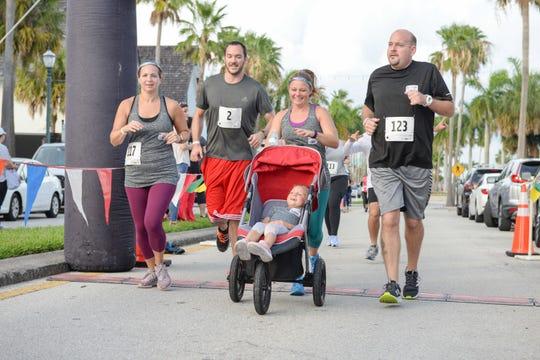 Alison Smolarek, left, Ryan Atkins, Kara Smolarek pushing Kailani and Joe Stuck run in the 2019 Sailfish Beer Mile in downtown Fort Pierce on June 14.