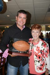 Travis Leonard, left, and Linda Evans show off a football signed by Khalil Mack at the LifeBuilders of the Treasure Coast's Golf Tournament and Cocktail Par-Tee.