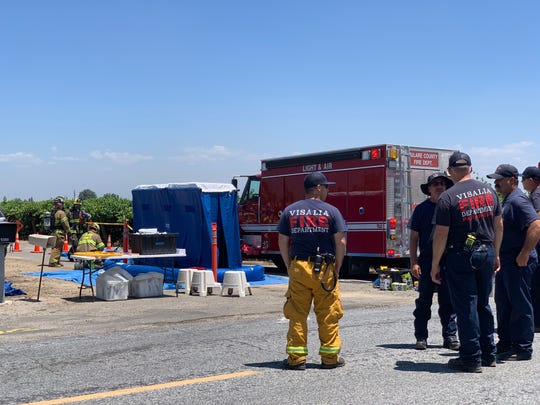 Hazmat crews are starting mass decontamination for the 63 fieldworkers sprayed with pesticides.