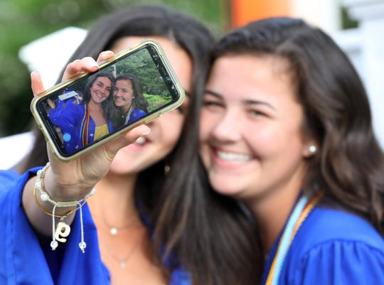 From left, Gabrielle Marino and Colleen McCarthy take a selfie before North Salem graduation at Caramoor in Katonah June 17, 2019.