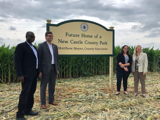 County Executive Matt Meyer poses with New Castle County officials and members of the task force at the site of a new park in Middletown.