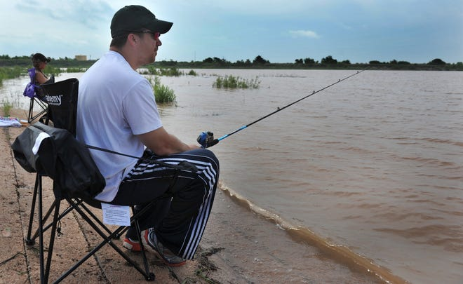 In this 2015 photo, Michael Hawkins fishes from a boat ramp at Lake Kickapoo. Wichita Falls inspectors went to the lake in March and found a majority of the riprap surface of the dam had sloughed off into the water.
