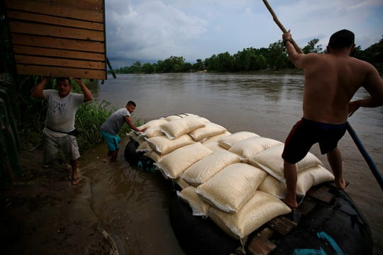 Raftsmen set off across the Suchiate River with a load of Mexican corn for a Guatemalan buyer, in Ciudad Hidalgo, Mexico, Monday, June 17, 2019.