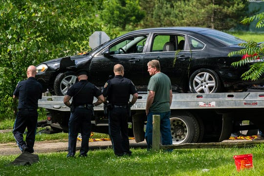 Police remove a black sedan from the Kalamazoo River near Verburg Park, on Tuesday, June 18, 2019, after finding the bodies of a mother and child inside the submerged vehicle, in Kalamazoo, Michigan. The car went into the river the night before.