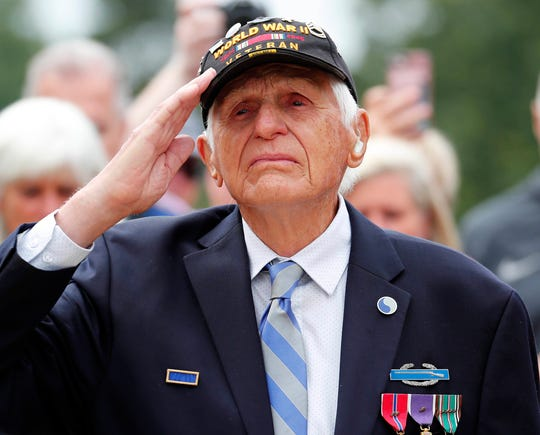 Steve Melnikoff salutes during a ceremony at the Normandy American Cemetery and Memorial on Tuesday.