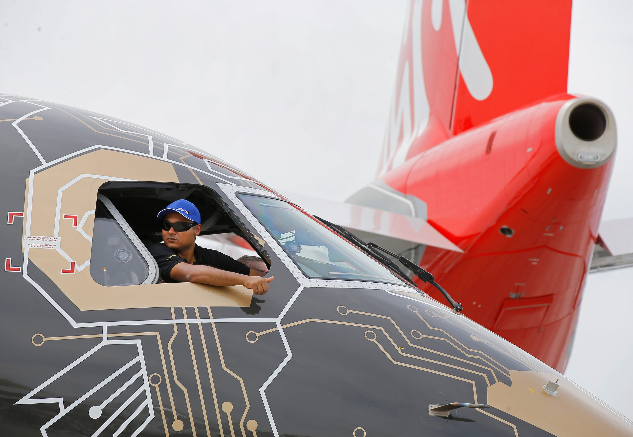 A pilot of an Embraer Profit Hunter E195-E2 makes the thumbs up sign as he on the tarmac at Paris Air Show, in Le Bourget, east of Paris, France, Tuesday, June 18, 2019. The world's aviation elite are gathering at the Paris Air Show with safety concerns on many minds after two crashes of the popular Boeing 737 Max. (AP Photo/Michel Euler) ORG XMIT: MEU110
