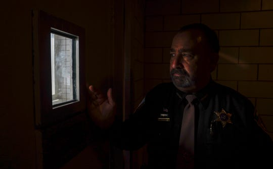 Dane County, Wis., Sheriff David Mahoney looks through a small window in a solitary confinement cell at the county jail in Madison.