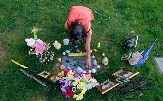Melany Zoumadakis arranges photos and flowers that she brought to the grave of her daughter, Tanna Jo Fillmore, on April 26, 2019, in Salt Lake City.