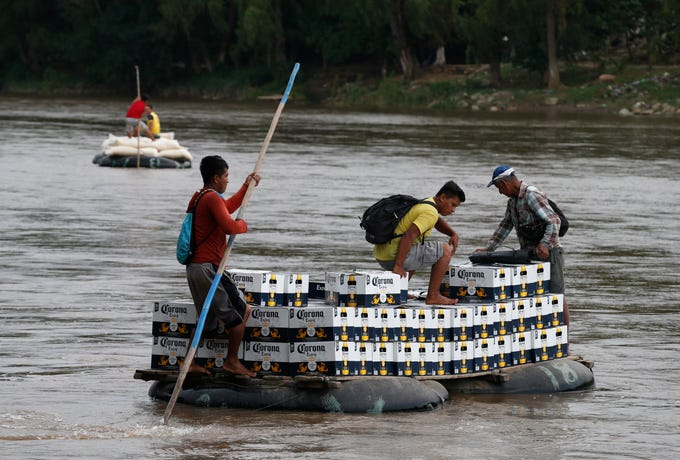 Raftsmen carry a load of Corona beer across the Suchiate River on an inner tube and plank raft, near Ciudad Hidalgo, Mexico, Monday, June 17, 2019, on the border with Guatemala. Along the Suchiate, merchants and politicians expressed concern that an immigration crackdown could impact the free flow of cross-border commerce on which communities on both sides depend. (AP Photo/Rebecca Blackwell)