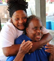 Patricia Murray sneaks up behind Billie Lewis to give her friend a hug Wednesday at the free Juneteenth lunch provided by a Saved to Serve, a Bible study class that meets at GV Daniels Recreation Center where lunch was served. The ministry began in September, has about 15 members and is led by Pastor James Webbs. They participated in several holiday projects, president Dorothy Drones said, including feeding six families and also helped a young boy attend summer activities at the rec center by paying his fees.