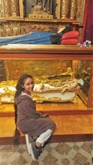 Harley Flores sits in front of a display case with the incorrupt body of Sor María de Jesús de Ágreda on top of the case. Harley, an Abilene High School student, was baptized in the basilica in Agreda, Spain, where Sor Maria also was baptized.
