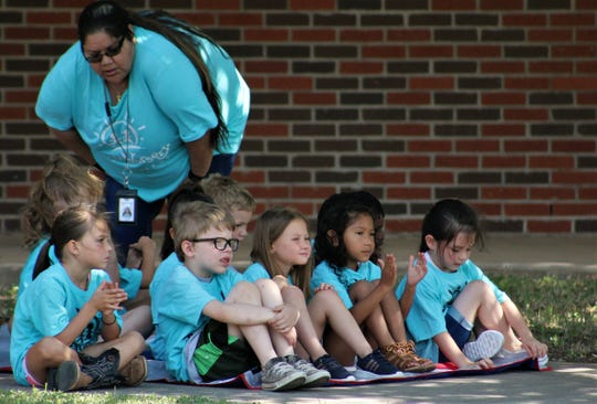 Dora Rosales, who has been a teacher at the downtown Day Nursery of Abilene since 1997, hovers over a group of youngsters from that facility at Wednesday's announcement of a fourth location at the former College Heights Elementary School.
