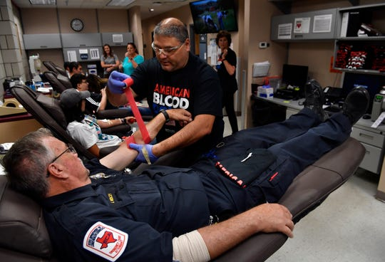 Jerry Medley, an Abilene Fire Department captain at Station No. 1, watches as blood bank technician Freddie Sosa wraps a bandage around his arm Wednesday at the Meek Blood Center. The Rodney Holder Guns and Hoses Blood Drive contest between police and firemen went until 7 p.m.