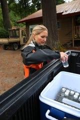 Anne Moen places jars containing water from Island Lake in a cooler in the back of her truck. The jars from various lakes will be sent to a lab to test for dangerous bacteria.