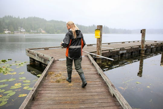 "Environmental health technician for Kitsap Public Health District Anne Moen walks out on the boardwalk at Kitsap Lake to get a sample of deeper water with her ""U-scoop"" tool."