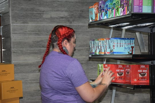 Employee Megan Lonzano stocks shelves at the new Naturally 4 Paws Poulsbo location.