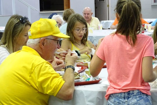 Diners enjoy their meals in the Youth Building during the annual Bucyrus Kiwanis Club Chicken Barbecue on Wednesday at the Crawford County Fairgrounds.