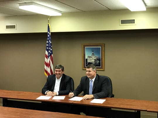 Zanesville-Muskingum County Port Authority Executive Director Matt Abbott, right, and AMG Vanadium President Hoy Frakes go through the paperwork for the purchase agreement of land at Eastpointe Business Park.