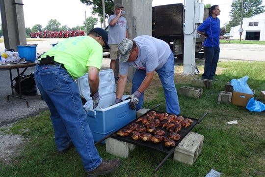 David Koepke and Tom Holtshouse prepared to remove cooked chicken portions from the grate during the annual Bucyrus Kiwanis Club Chicken Barbecue on Wednesday at the Crawford County Fairgrounds.