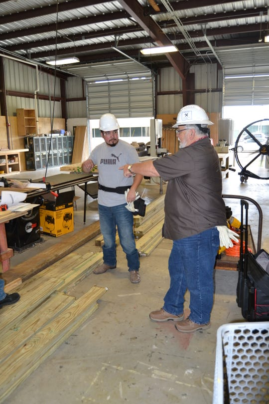 Alex Bayarena (right) instructs student Fernando Reyes on saw techniques during the Rebuild Texas Carpentry Skills Training program.