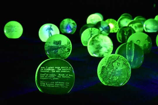 This is a detail of Jo Yarrington's installation 'Uranium Game,' created with uranium glass, photo decals, blacklight, aluminum oxide, grout, and featuring an audio player playing a poem by Allen Ginsburg.  It is part of  WheatonArts: Emanation 2019.'
