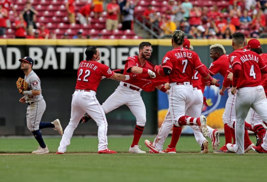 The Cincinnati Reds celebrate with left fielder Jesse Winker (33) after his hits the game-winning RBI single in the bottom of the ninth inning of the MLB interleague game between the Cincinnati Reds and the Houston Astros at Great American Ball Park in downtown Cincinnati on Wednesday, June 19, 2019. The Reds completed a sweep of the Astros on a walk-off single by Jesse Winker.
