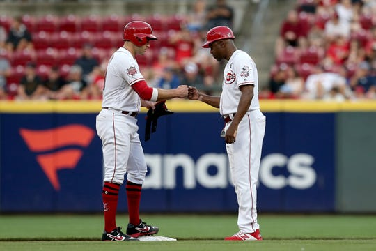 Cincinnati Reds first baseman Joey Votto (19) bumps first with Cincinnati Reds first base coach Delino DeShields (90) after hitting a double in the third inning of the MLB interleague game between the Cincinnati Reds and the Houston Astros at Great American Ball Park in downtown Cincinnati on Tuesday, June 18, 2019.
