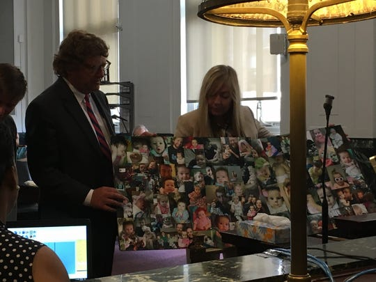 Attorneys for Anthony Worthington hold up two posters featuring photos of his 13-month-old daughter, Raegan, who died Jan. 4, 2019 after ingesting fentanyl in their home. Worthington was sentenced Wednesday, June 19, 2019 in Hamilton County Common Pleas Court.