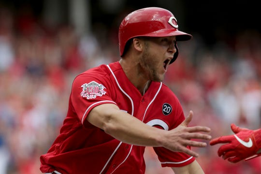 Cincinnati Reds center fielder Nick Senzel (15) begins to celebrate after crossing the plate as the game-winning run in the bottom of the ninth inning of the MLB interleague game between the Cincinnati Reds and the Houston Astros at Great American Ball Park in downtown Cincinnati on Wednesday, June 19, 2019. The Reds completed a sweep of the Astros on a walk-off single by Jesse Winker.