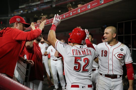 Kyle Farmer (52) is high fived in the dugout after a home run in the seventh inning of the MLB interleague game between the Cincinnati Reds and the Houston Astros at Great American Ball Park in downtown Cincinnati on Tuesday, June 18, 2019. The Reds won 4-3.