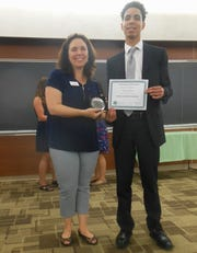 Rachel Lyons, Chairperson of the Rutgers 4H Youth Development Department, presents a Best in Room award to Victor Heras of Rahway.