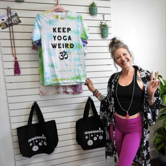 Cindy Kostecki of Crowtown Yoga shows off some items in the new boutique area of her yoga studio.