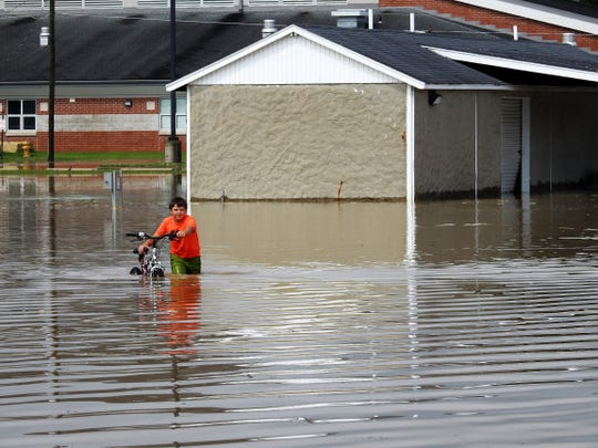 Sebastian Calvo, 9, pushes his bicycle through flood waters behind Ridgewood Middle School in June. About 7 inches of rain fell in a few short hours from late June 18 to early June 19. The village is fairly back to normal, but many people are still dealing with the aftermath.