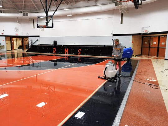 Eliza Haynes, a part-time custodian, vacuums water from the gymnasium floor at Ridgewood Middle School. Water damaged lower level classrooms as well. Sandbags were placed at doors and other spots in case more rain comes.