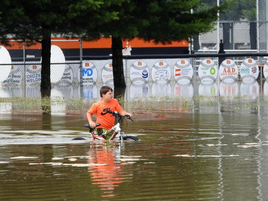 Sebastian Calvo, 9, pushes his bicycle through flood waters behind Ridgewood Middle School that covered the baseball and softball fields. Water also damaged some lower level classroom and the gymnasium floor inside the building.