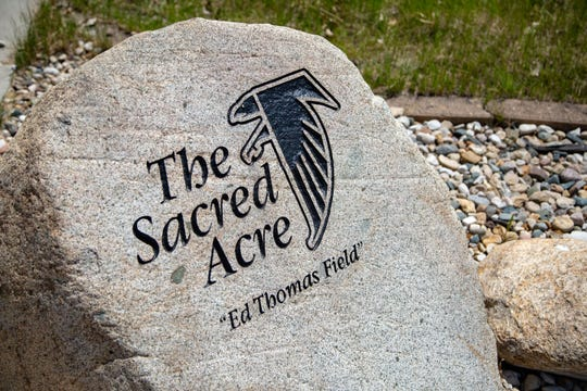"A stone outside Aplington-Parkersburg High School's Ed Thomas Field, named after the school's late football coach, marks ""The Sacred Acre."""