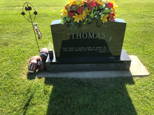 The tombstone for Ed Thomas in Parkersburg includes five footballs.