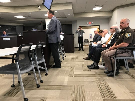 Macomb County Sheriff Anthony Wickersham, seated in uniform, looks at county commissioners as they listen to a proposal for a new $371-million jail and sheriff's office in Mount Clemens during a board meeting June 19, 2019.
