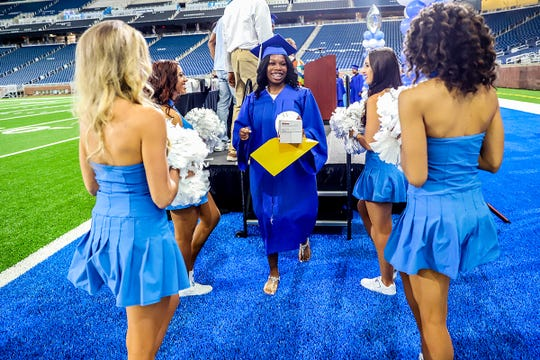 Selena Clark, walks off the stage in between Detroit Lions cheerleaders after accepting her diploma, during the Detroit Lions Academy 8th grade graduation held at Ford Field in Detroit on Wednesday, June 19, 2019.