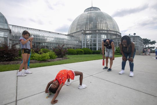 Lauren Hoskins, 8, left, of Iowa, films her sister Makenzie Brown, 4, of Iowa while she performed a backbend in front of the Anna Scripps Whitcomb Conservatory on Belle Isle, Wednesday, June 19, 2019, as her grandmother Tia Turner, 44, of Detroit, right, laughs with her partner Fanciska Stasiewicz, 35, of Hamtramck.