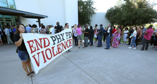 People line up near protesters outside a venue for a community meeting, Tuesday, June 18, 2019, in Phoenix. The  meeting stems from reaction to a recording that surfaced recently of Dravon Ames and his pregnant fiancee, Iesha Harper, having had guns aimed at them by Phoenix police during a response to a shoplifting report.