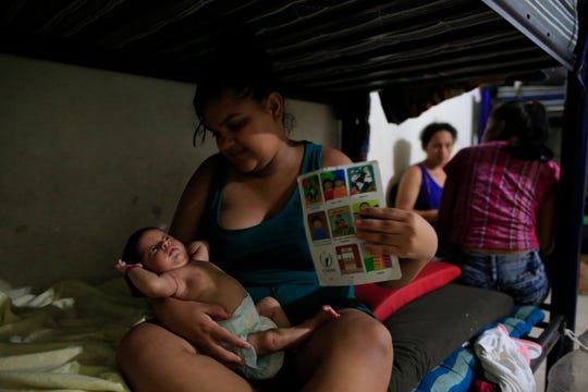 Honduran migrant Clarisa Amanda Webster, 20, uses a paper to fan her 2-month-old daughter Melani, who was born soon after she arrived with her husband in Tapachula, Mexico, as they rest in a dormitory on a stiflingly hot night, at the Good Shepherd migrant shelter.