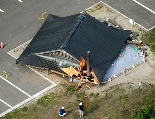 The roof of the wooden sumo building falls on the site of the Oizumi Elementary School in Tsuruoka, Yamagata prefecture, northwestern Japan, Wednesday, June 19, 2019, after an earthquake.