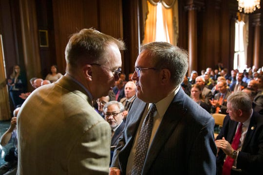 Acting White House Chief of Staff Mick Mulvaney, left, shakes hands with EPA administrator Andrew Wheeler after Wheeler signed the Affordable Clean Energy Rule at the Environmental Protection Agency, Wednesday, June 19, 2019, in Washington.