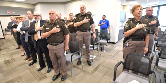 Macomb County Sheriff Anthony Wickersham, center-left, his command staff and others stand for the Pledge of Allegiance during the meeting to consider the jail proposal.
